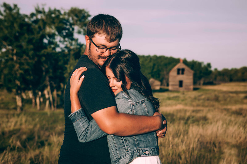couple lovingly embrace with eyes closed in field
