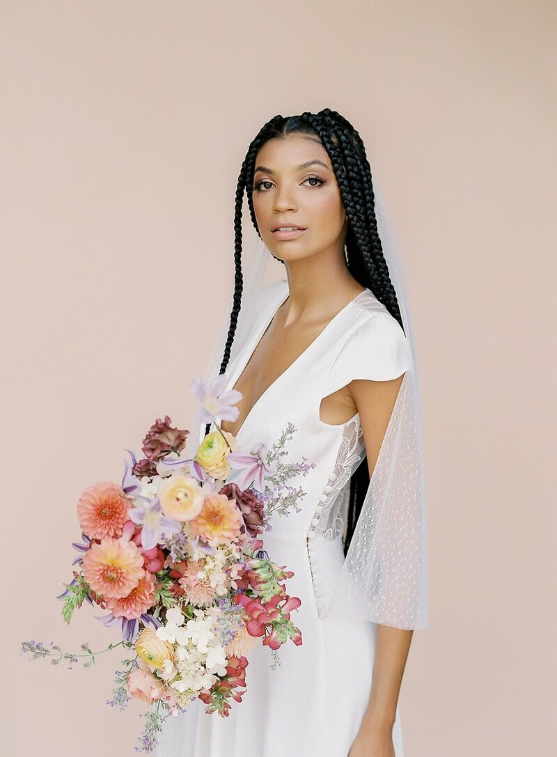 black-bride-wearing-white-dress-with-veil-holding-a-colorful-bouquet (1)