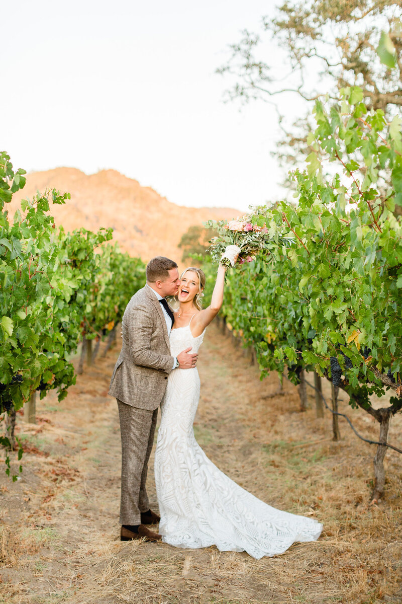 Bride and groom celebrating in a vineyard in Napa Valley, California. Wedding photo taken by Cheers Babe Photo.