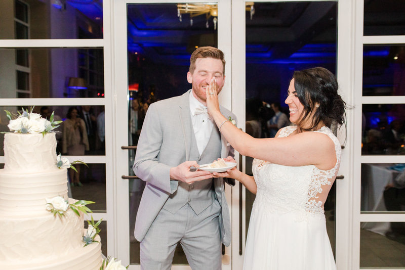 bride shoving cake in grooms face  at Stone House at Stirling Ridge Maryland Wedding by  Costola Photography