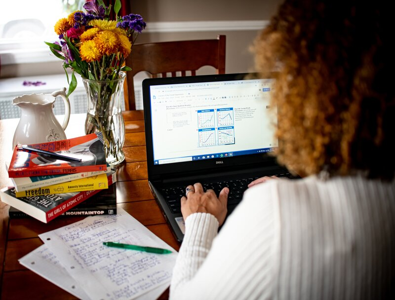 Woman with back to camera typing on a computer at the dining room table with flowers.