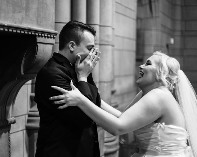 Groom reacts when he sees his bride in her dress at the Cathedral of Learning in Pittsburgh, PA