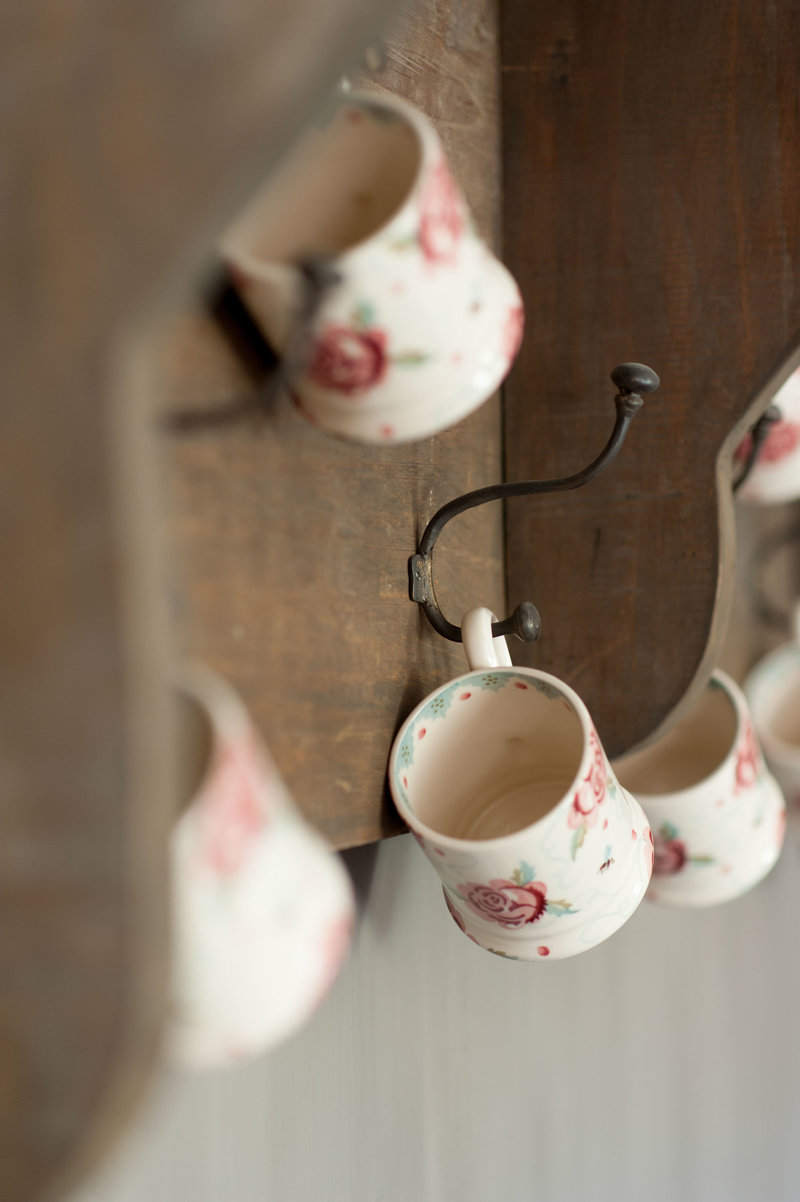 Emma Bridgewater mugs hanging from wooden rack by Hoffz Interior in the kitchen of an English cottage, project by Arte di Vita Interiors.