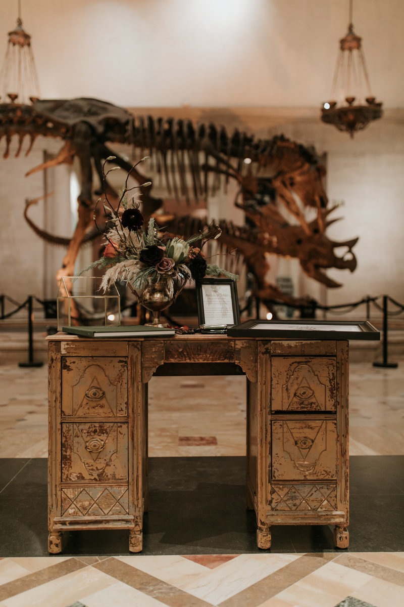Natural History Museum wedding welcome table  in front of trex with dramatic floral centerpiece