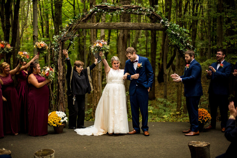 Bride raises arm in voctory at the end of Majestic Woods wedding ceremony