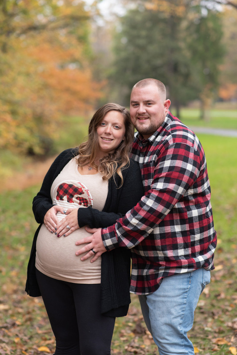 Husband & Pregnant Wife snuggled together in wooded area