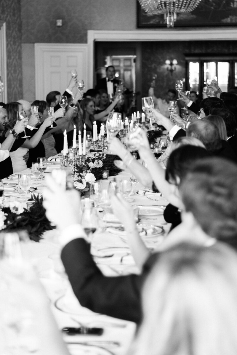 Guests of wedding raise their glasses to cheers at wedding reception