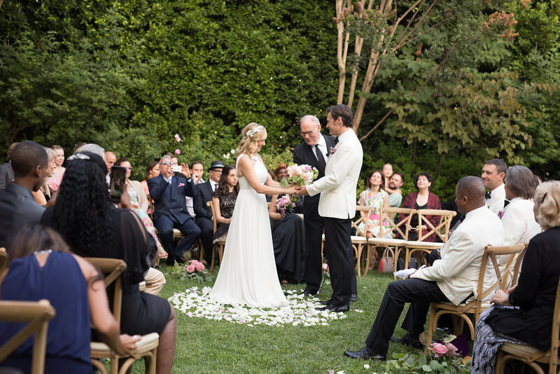Bride and groom take their vows atop a cirle of white rose petals surrounded by guests