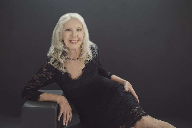 80 year old beauty with classic makeup in a black dress in a studio