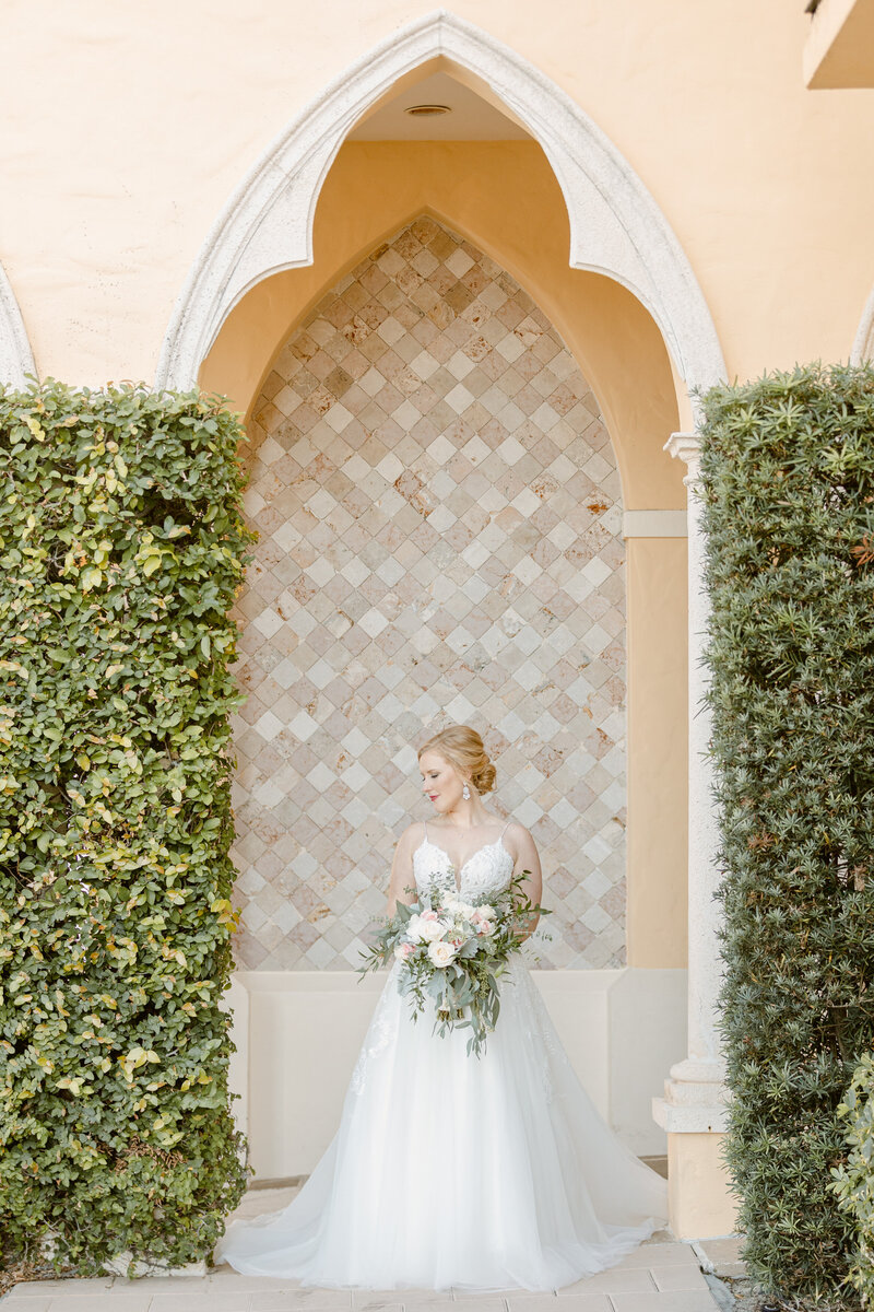 Beautiful bride poses under archway with her bouquet on wedding day