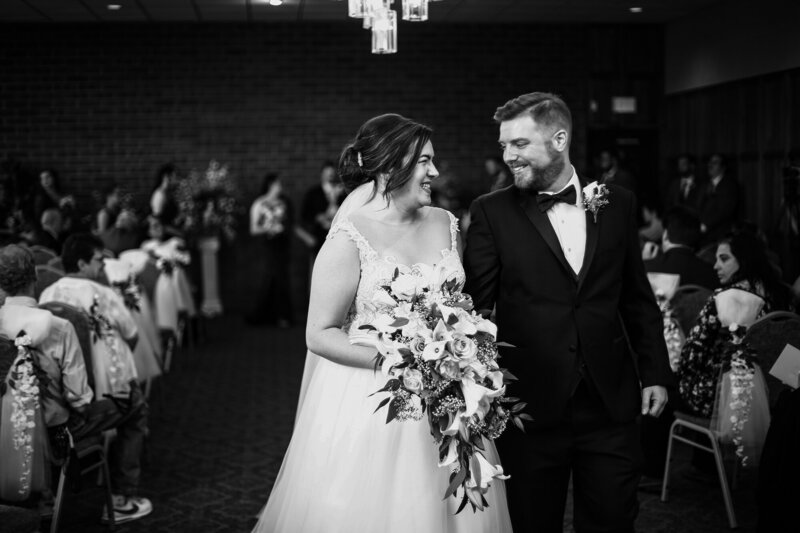 Bride and groom smile at each other during recessional at Zem Zem Shrine Club wedding
