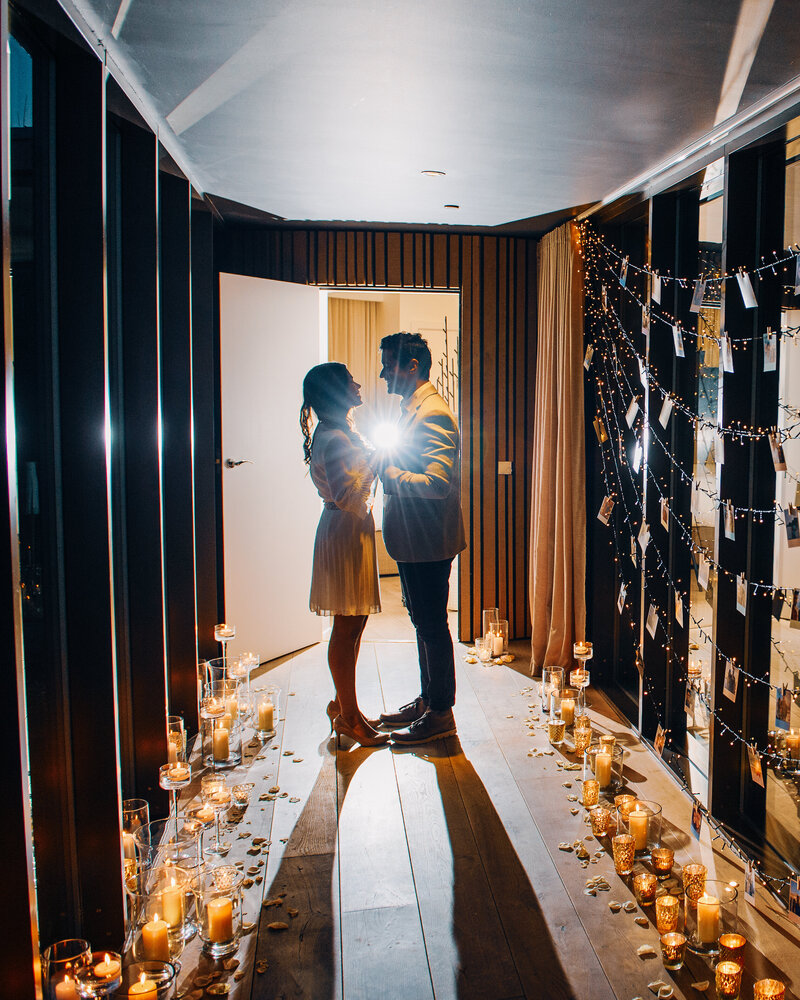 A couple stand holding hands in a hallway with fairy lights and polaroids with candles for a luxury wedding proposal.