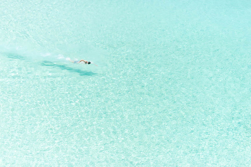 person swimming in the blue waters of anguilla
