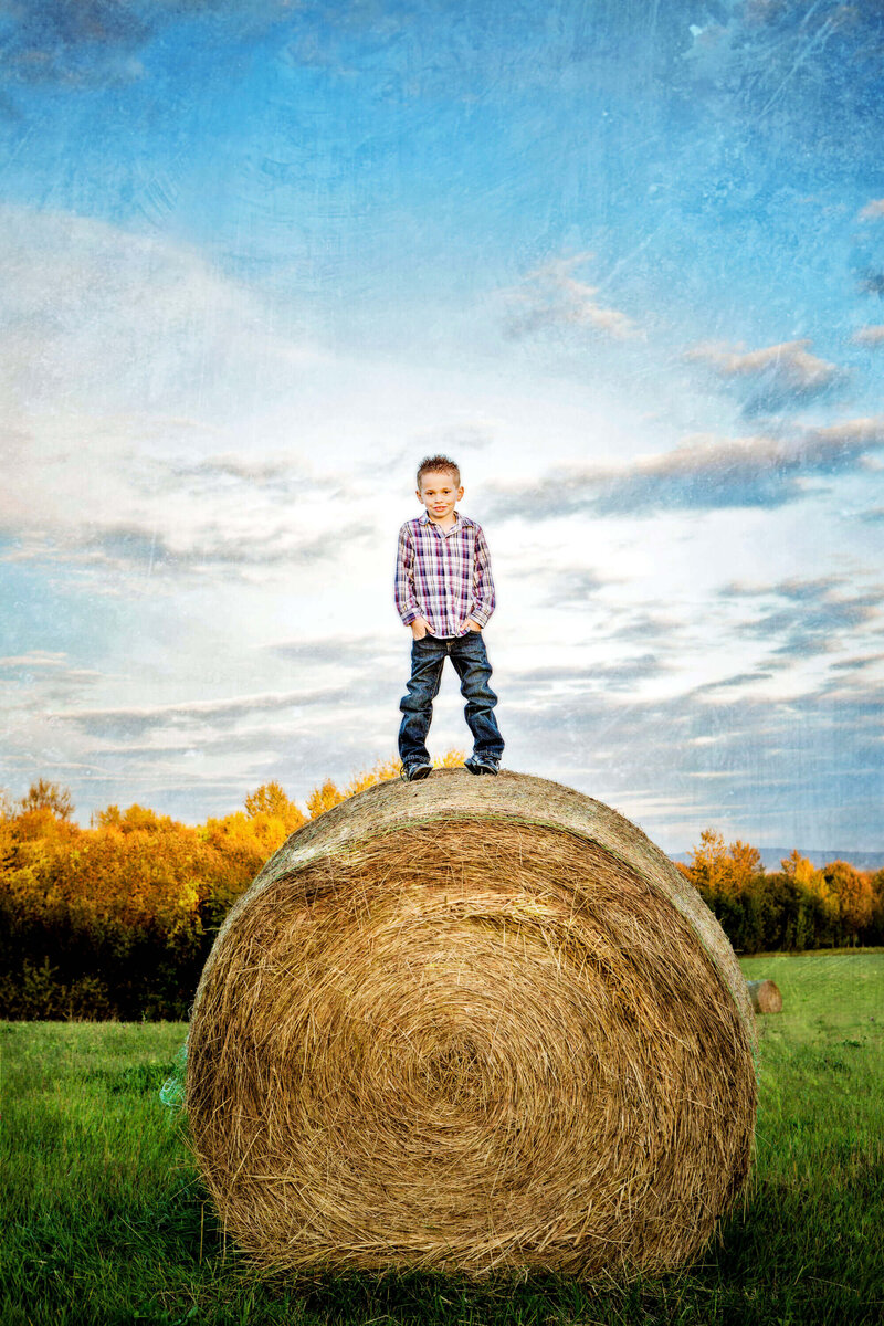 little boy on top of large round hay bale