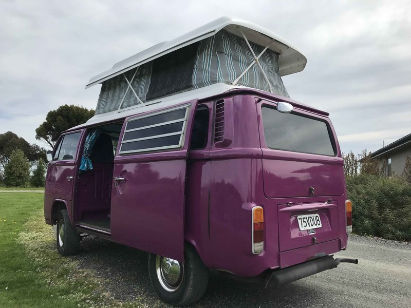 Outside view of left side with sliding door and pop top extended of Pippi, purple retro kombi van from NZ Kombi Hire