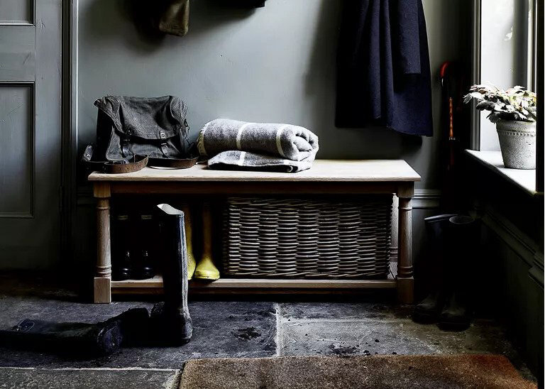 A boot room wooden bench with a pair of wellingtons in front.