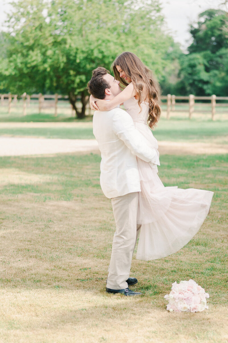 Groom lifts his bride up and twirls around in the grounds of Eastington Park