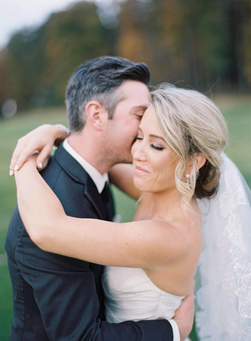 Bridal Portrait of Groom kissing smiling bride lacy veil black tie tuxedo at Seven Oaks Country Club | Pittsburgh Wedding Photographer | Anna Laero