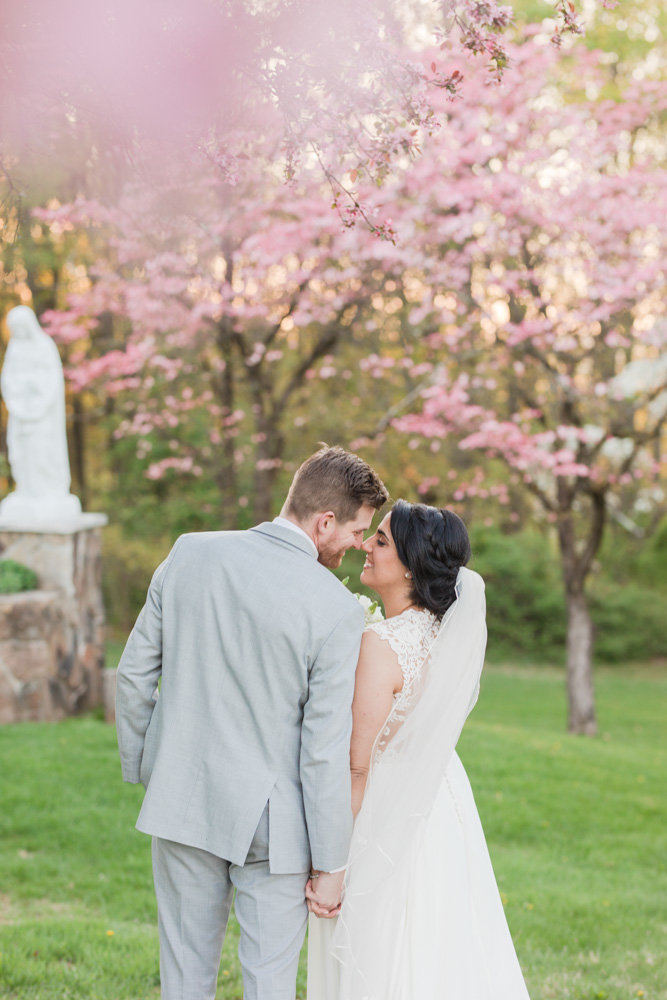 bride and groom kissing under pink trees  at Stone House at Stirling Ridge Maryland Wedding by  Costola Photography