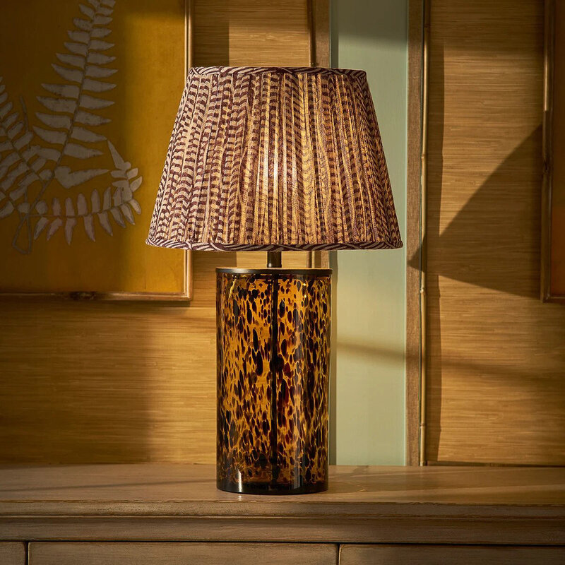 A tortoiseshell tall glass lamp from Oka is pictured by a wooden wall.