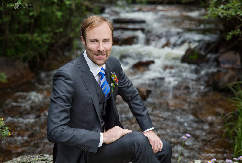 Groom poses next to Elk Creek at Mountain View Ranch Wedgewood Weddings