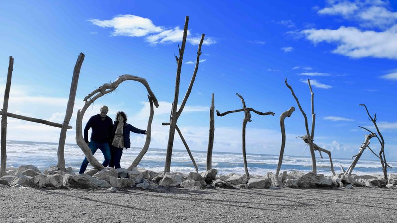 Lynda and Warren standing behind the Holitika sign made from driftwood on the beach in Hokitika, South Island, New Zealand