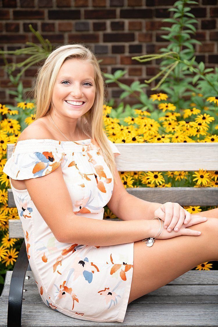 High school senior girl in off the shoulder flowered dress sitting on wooden bench in front of Black-eyed Susan flowers at Mellon Park in Pittsburgh, PA