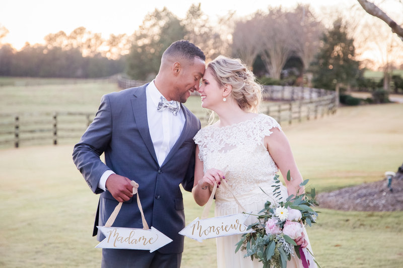 An interracial couple holds signs at their wedding at the Venue at Murphy Lane by Jennifer Marie Studios, best Atlanta wedding photographer.