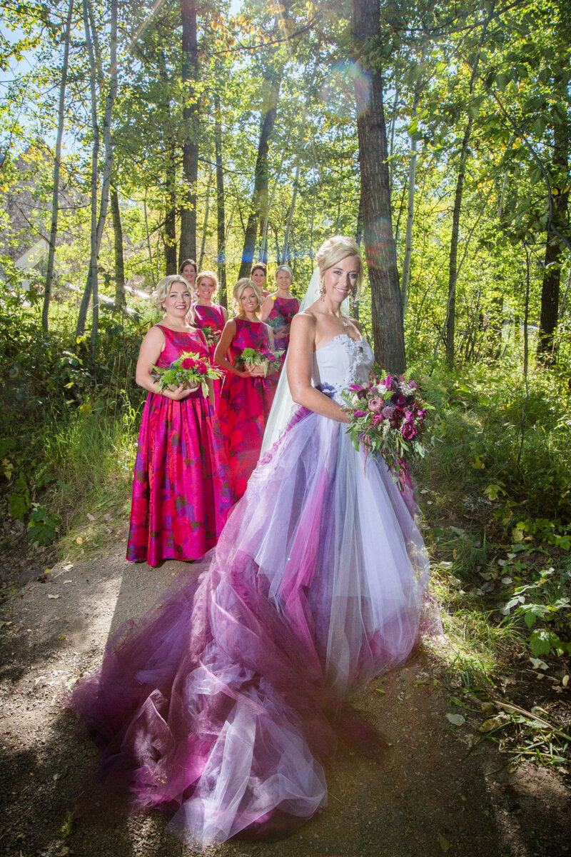 testimonial photo, a bride wears a pink and purple tinted wedding dress with her bridesmaids in the background