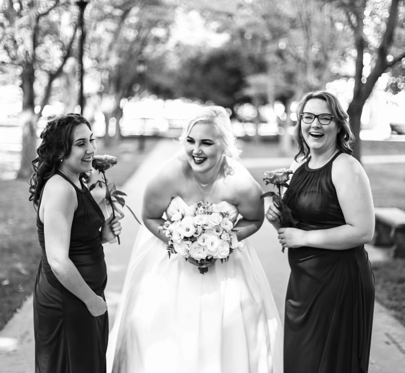 Bride laughs with her bridesmaids outside the Cathedral of Learning in Pittsburgh, PA