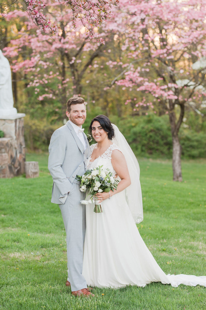 bride and groom under pink trees  at Stone House at Stirling Ridge Maryland Wedding by  Costola Photography