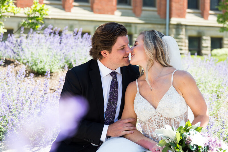 bride and groom kissing with purple flowers at st. Ignatius school cleveland