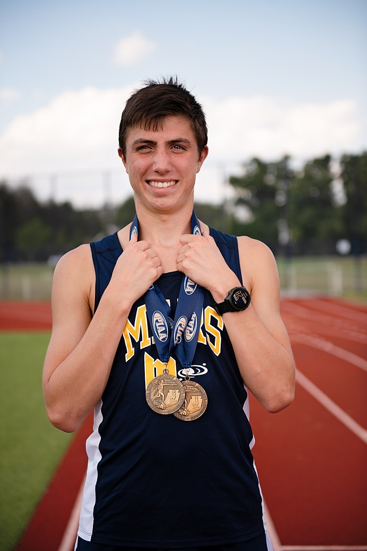 High school senior boy in track uniform, gold medals around neck standing on track at Mars High School in Pittsburgh, PA