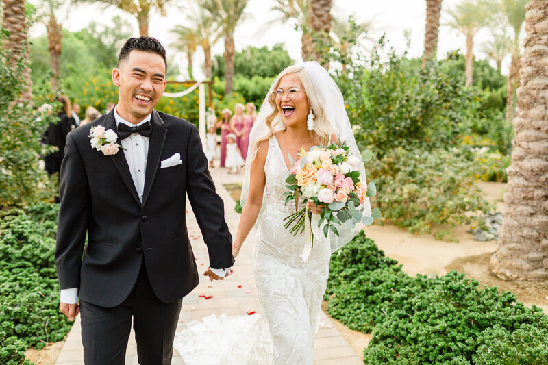 Groom and bride's recessional at their ceremony on their wedding in Palm Springs. Photograph taken by Cheers Babe Photo.