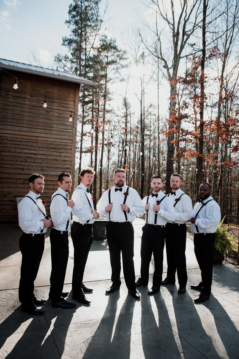 groomsmen posing with the barn at cedar hill in the background