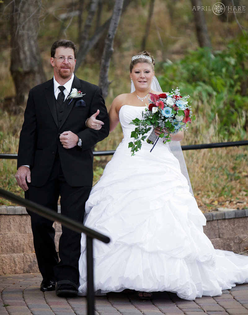 Father walks with his daughter down aisle to Aspen Terrace at Pines at Genesee