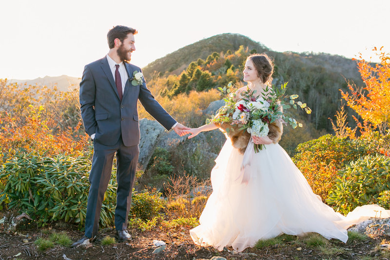 Portrait of the bride and groom holding hands and looking at each other while the bride is holding a bouquet in her hand with a beautiful background of mountains and greenery at the Twickenham house in Jefferson NC