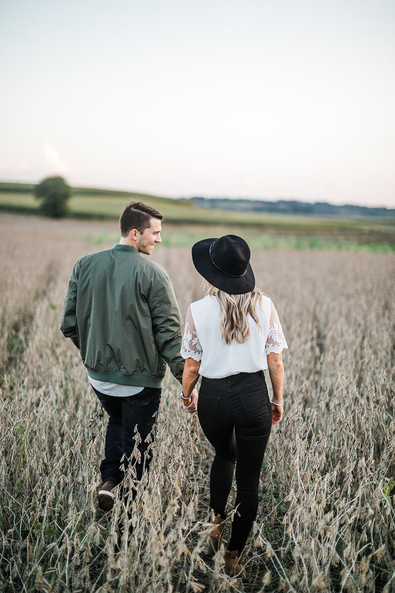 Engagement Photo of Couple Walking Through Field at Dusk at McConnells Mills, PA