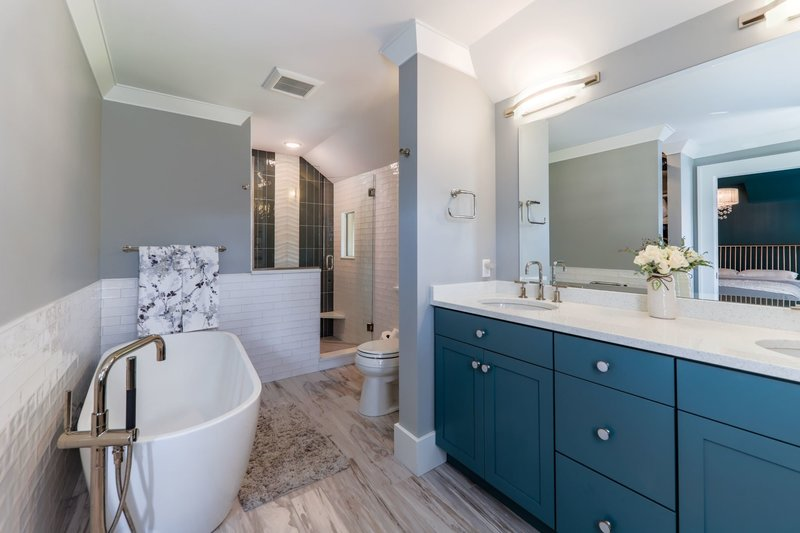 freestanding bathtub with blue cabinetry