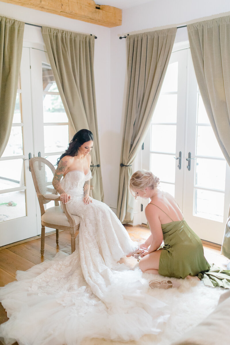 bridesmaid helping bride put on shoes at French Inspired Private Estate wedding in charlottesville virginia by costola photography