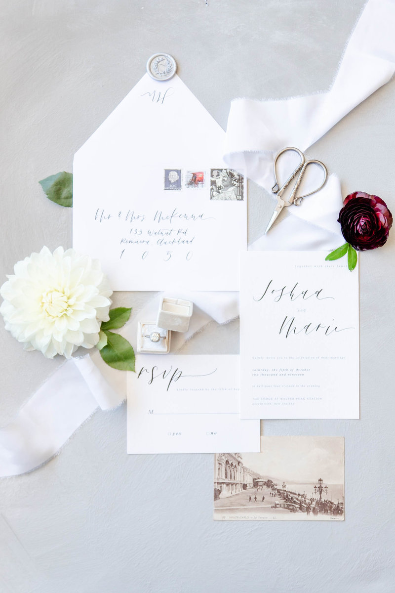 An arrangement of invitations with ribbon flowing between