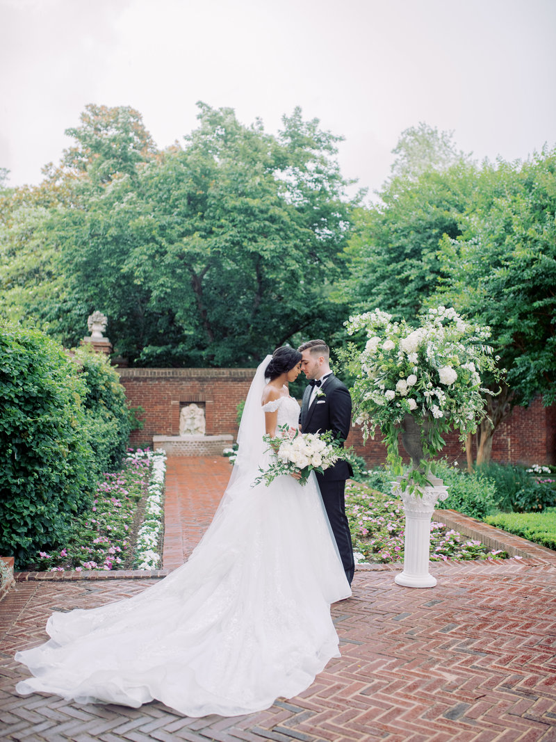 Bride and groom  with white  garden style flowers in Maryland