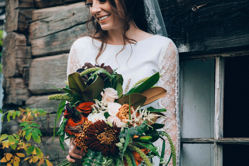 bride by old building with bouquet of flowers