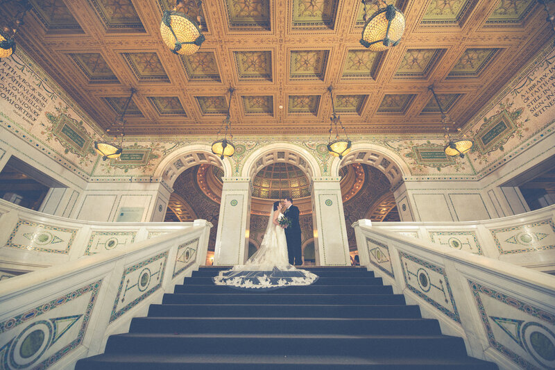A bride and grooms on the steps of the luxury Chicago Cultural Center with beautiful architecture and archway entrance behind them.