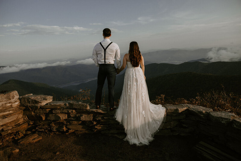 bride and groom standing on cliff with mountains in background