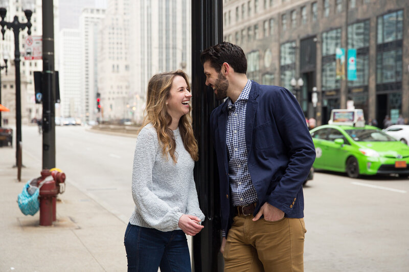 couple laughing and smiling after woman gasping from surprise engagement downtown chicago mag mile
