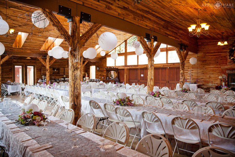 Long rows of white tables inside Mountain View Ranch for a rustic wedding reception in a Colorado barn