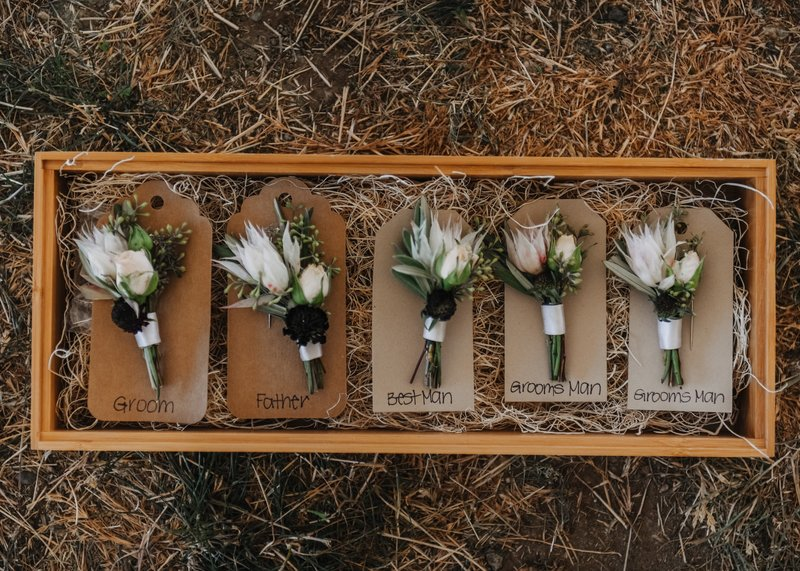 Rustic blush and burgundy boutonnieres in a wooden box