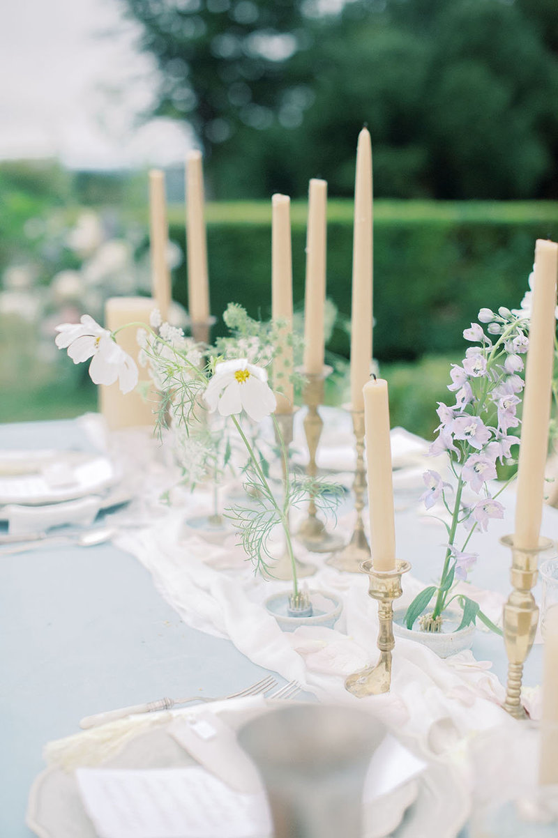 Flowers overflowing from a yellow table with gold candlesticks