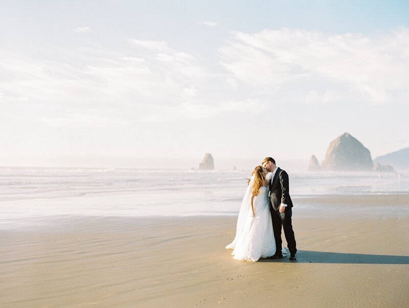 bride and groom at Canon Beach kissing